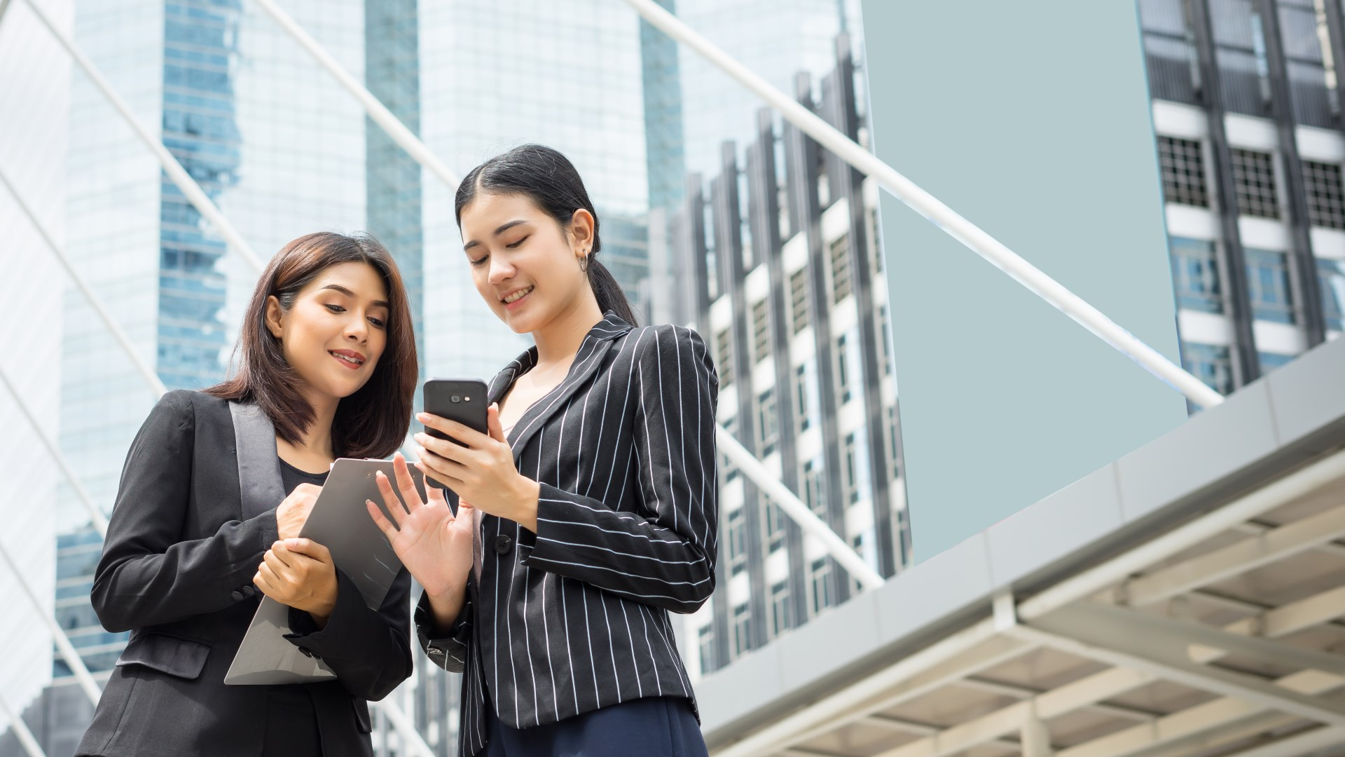 Two business woman standing using smartphone and discussing in front of the office. Business working concept.